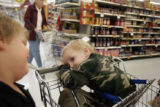 Dakota Givens, 7, left, smiles at his brother Carson while the two went shopping with their mother...