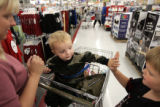 Carson Givens, cq, center, gives his brother Dakota, cq, a high five while shopping with their...