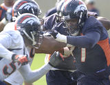 Bronco veteran Dwayne Carswell (right) fights off Keith Burns and Mario Fatafehi during  practice...