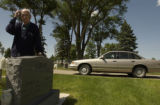 (BRUSH, Colo., June 2, 2004) Harold stands at his own headstone where his wife is buried and...