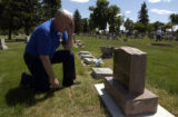 (BRUSH, Colo., June 2, 2004) Stan concentrates on reading the newly dedicated memorial headstone...