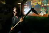 Bob Cote, cq, president of Step 13 holds a hoe in front of a mural of a bar scene that is painted...