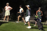 L to R: Golfers Janice Campbell and Tracey Blake get help watching a ball from caddies Vincenzo...