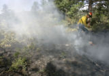 Hartsel firefighter Scott Hutcheson, 24, cq, works with a fire crew to mop-up hot spots from the...