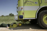 Firefighter Ryan Steiger, (cq), takes a 5-minute nap in the shade of his firetruck southeast of...