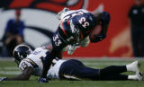 JPM0870-- Denver Broncos Ron Dayne, #33, leaps over San Diego Chargers safety Terrence Kiel, #48,...