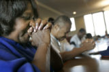 Hurricane Katrina evacuee Betty Daggs (cq, left) of New Orleans prays with her husband Lionell...