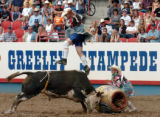 (GREELEY, COLO., JULY 2, 2004)    Bullfighter Lance Brittan, top, leaps over a fighting bull as...