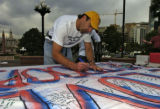 Scott Johnson (cq), of Denver, signs a support the troops banner Wednesday afternoon September 21,...