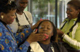 Clorissa Fontenot (cq) receives a facial from Mattie Harris (cq), left as Dionna Overby (cq),...