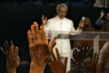 Hundreds of Christian faithful raise their hands in praise as evangelical preacher Benny Hinn, in...