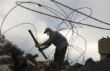 (Greeley, Colo., July 19, 2004) Tomas Landin (cq), of Greeley, helps clear burnt debris from the...