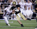 University of Colorado quarter back, Joel Klatt, center, makes a run for a first down in the...