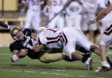 University of Colorado quarter back, Joel Klatt, left, gets tackeled after a first down run in the...
