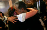 Byron Johnson's daughter Jacquelyn Benton is huged by a close friend after a memorial service for...