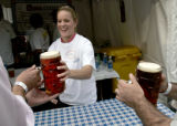 Jessica Mackley (cq), 26, a metro volunteer at Denver's annual octoberfest serves up stiens of...