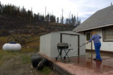 Crystal Majors washes fire retardant from her deck Tuesday, September 20 after a wildfire burned...