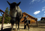 (ROCKY MOUNTAIN NATIONAL PARK , Colo. July 21,2004) Terry Humphrey (cq) prepares a horse for a...