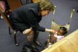 Salvation Army Major Linda Manhardt, cq, greets Kyira Scott, cq, 8 months, during a farewell party...