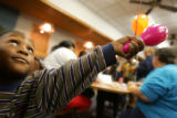 Roncarin Hall, 2, plays with a balloon during a farewell party for Katrina Evacuees at Lowry. ...