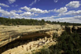 A ranger-led tour makes their way through the Cliff Palace site, which is tucked under an alcove...