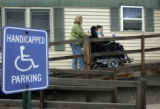 Debbie Miller (cq) guides her son Brian's wheelchair up the ramp and into their mobile home in...