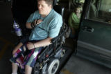 Debbie Miller (cq) tries to figure out why her son Brian's wheelchair will not slip into it's...