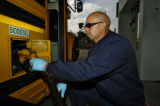 Devin Pierce (cq) fills a Denver school bus with biodiesel Tuesday morning October 11, 2005 at the...