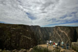 Visitors take in the spectacular view from the Painted Wall View Overlook in the Black Canyon of...