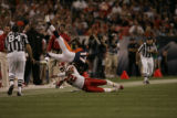 Denver Broncos wide receiver Darius Watts (17) gets upended by Kansas City's Dexter McCleon (22)...