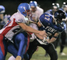 Lyons wide reciever, Jason Terranova, right #17, gets pulled down by Lyons defenders, Joe McKay,...