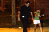 DENVER, COLO., PHOTO TAKEN July 11, 2004 - A woman is escorted by a Denver police officer from a...