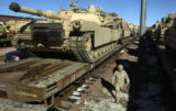 FORT CARSON, COLO.-February 2,2005- Capt. Ken Woods walks past an M1A2 Tank during rail loading...
