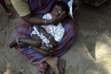 (1/18/05, Singarathoppu , India)  A mother comforts her sleeping child as they wait their turn to...
