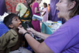 (1/18/05, Singarathoppu , India)   Teri Lynn inspires a young patient to open wide during his...