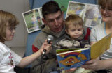 (FORT CARSON, Colo., February 1, 2005) Pfc. Ryan Healy reads while his daughter, Ashley...