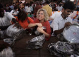 (1/26/05, Pondicherry, India)  Cheryl Bencala tries hard to pry two plates apart so they can be...