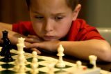 (DENVER Colo., February 13, 2005) Kyler Kirk, 8 years old from Lonetree, looks at the chess board...