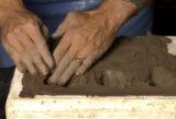 Artist Barry Rose presses terracotta clay into a mold for a capital in his Denver studio Thursday,...