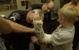 Sgt. Terry Maschka, left, asked first to sign Ryan's cast as Chief Paul D. Schultz, back center...