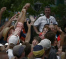 JPM0058 -Fans scramble for a hat thrown to them from the winner's circle podium by Sebastien...