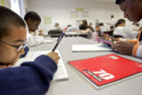 Bruce Randolph Middle School eighth grader Carlos Apodaca (cq, far left), 13, reads over the...