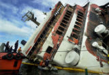 MLA206 - **  FILE  **The burnt Superferry 14 lies on it's starboard side as rescuers search for...