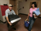 Ken Olsen (cq), left, carries the television while his wife Judy Olsen (cq), right, carries...