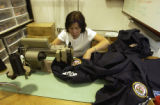 Infinity Gear Seamstress My Nguyen, sews FIMA patches on clothing which will be warn by search and...