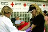 OAS102 - Red Cross worker Ginny Angerer, left, looks for a vein on the arm of Heidi Thomas of...