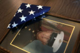 A folded flag sits on a portrait of fallen Marine Lance Corporal Evenor Herrera after his funeral...
