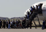 Refugees from New Orleans depart from 737's as they arrive at Buckley Air Force Base Sunday...