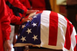 Members of the Winter Park Ski Patrol touch the casket of Rocky Mountain National Park Ranger Jeff...