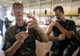Aiir National Guard Senior Master Sargeant Linda Baden (cq, left) of Aurora prepares a shot for...